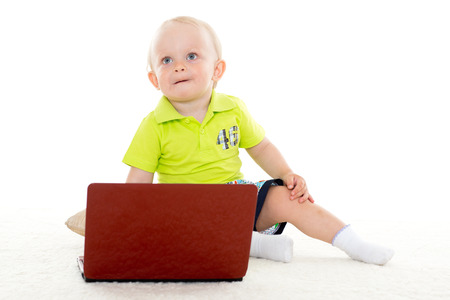 Sweet yearling baby boy  with laptop sits on the floor on a white background. photo