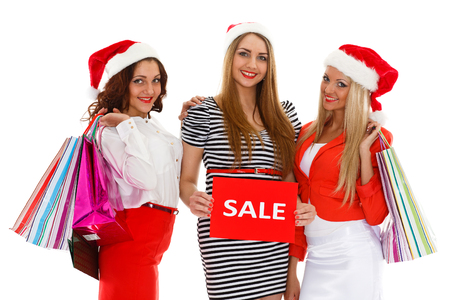 Three pretty young women in Santas hat with shopping bags stand on a white background photo
