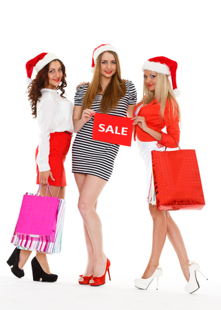 Three pretty young women in Santas hat with shopping bags stand on a white background. Christmas sale. photo