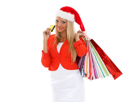 Pretty young woman in Santa's hat with shopping bags and credit card  stands on a white background photo