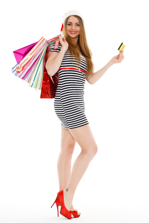 Pretty young woman in Santas hat with shopping bags and credit card  stands on a white background photo