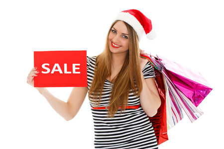 Pretty young woman in Santas hat with shopping bags stands on a white background photo