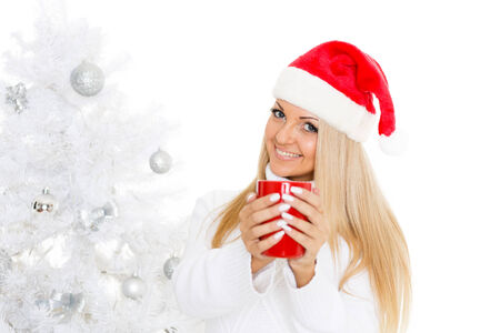 Young woman in Santa Claus cap  with red cup stands near Christmas tree on a white background. photo