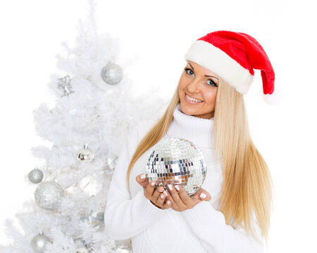 Young woman in Santa Claus cap  with mirror ball stands near Christmas tree on a white background. photo
