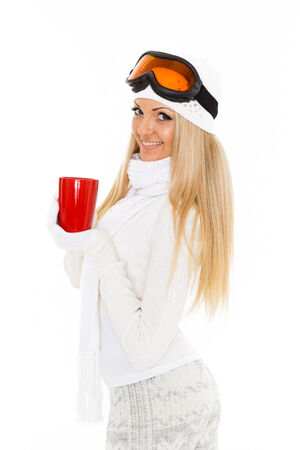 Young woman  in ski glasses  and  winter warm clothes  with red cup stands on a white background photo