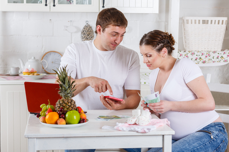 Pregnant family with money and babys clothes sit in the house kitchen. Family budget. photo