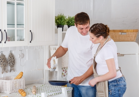 Happy pregnant woman and her husband cook food in the kitchen. photo
