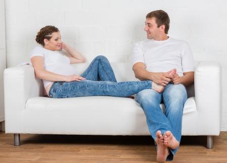 echtgenoot: De man doet massage van de voeten van de zwangere vrouw van het huis. Happy zwangere familie.