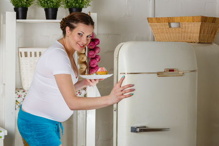 Hungry young pregnant woman stands near refrigerator and searches the food  photo