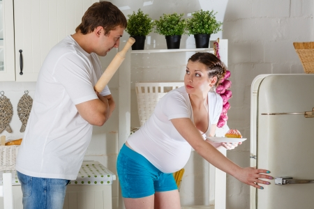 Hungry young pregnant woman and her husband standing near refrigerator in the kitchen  photo