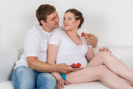 Happy pregnant family with strawberries sit on a sofa of the house  photo