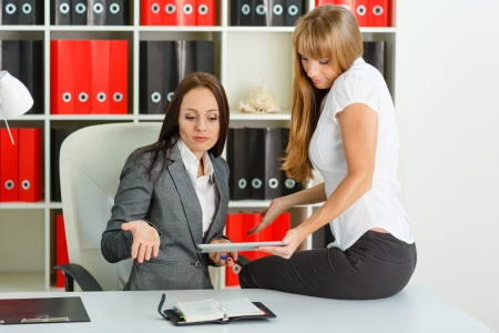 clothes organizer: Two young business women  with computer tablet and daily log sit in the office.