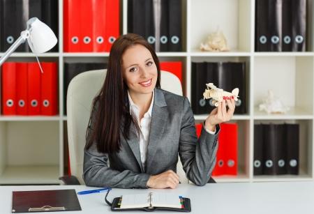 Zakenvrouw met een model van het vliegtuig zit op een werkplek in het kantoor. Reisbureau.