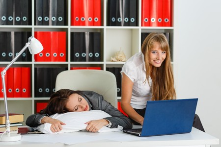 private information: Tired young business woman is sleeping on workplace in the office, another employee took advantage of the situation and is stealing private information from computer of competitor.