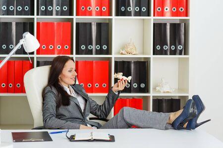 agencia de viajes: Empresaria con un modelo de avión se sienta en un lugar de trabajo en la oficina. Agencia de viajes.