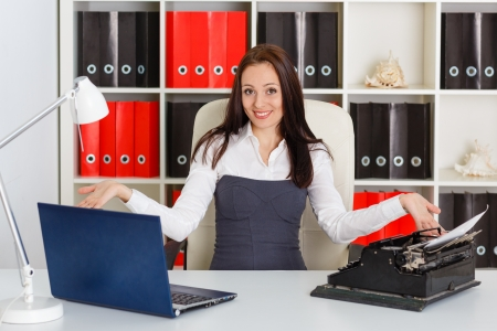 Young business woman  with notebook and old typewriter sits on workplace in the office. Progressing of technology. photo