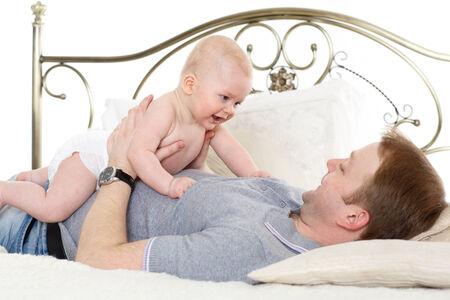 Young father with sweet child play on the bed on a white background. Happy family. photo