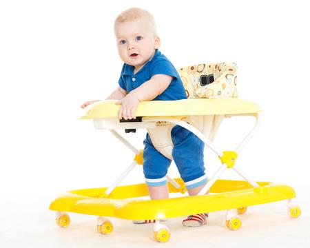 Het kleine kind leert lopen door middel van de baby walker op een witte achtergrond.
