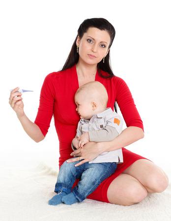 bebe enfermo: Madre joven con el term�metro y el beb� enfermo se sienta sobre un fondo blanco. Foto de archivo