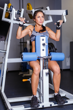 Sports woman doing exercises on power training apparatus in the gym. photo