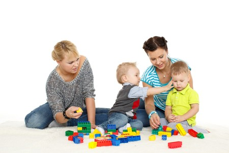 Two young happy mothers with children are playing  with developing toys on a white background. photo