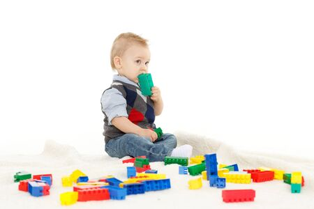 Sweet small boy  with toys on a white background. photo
