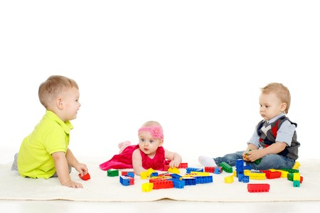 Happy little babies are playing with toys on a white background. photo