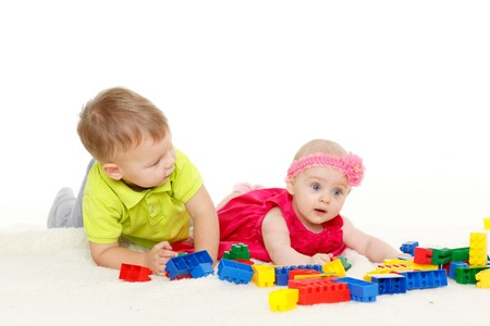 Little boy and girl are playing with developing toys on a white background. photo