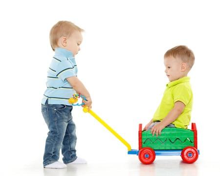 Los niños están jugando con carros de mano de juguete sobre un fondo blanco. Un niño pequeño se sienta en el carro de mano, otro niño le tira. Paseos a Merry. Foto de archivo
