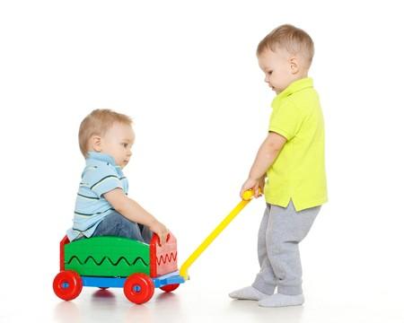 Kinderen spelen met speelgoed handkar op een witte achtergrond. Een kleine jongen zit in handkar, een ander kind hem trekt. Vrolijk rijden. Stockfoto