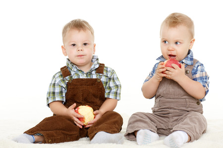 Two little boys with fresh apples sit on a white background. Healthy food. photo