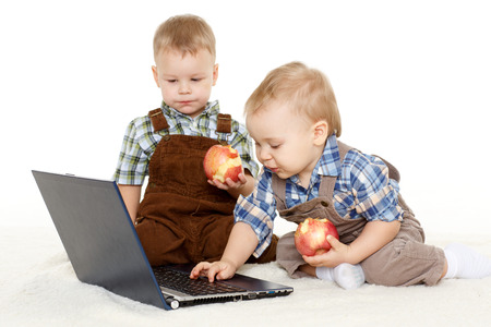 Two little boys with  with notebook and fresh apples sit on a floor on a white background. photo