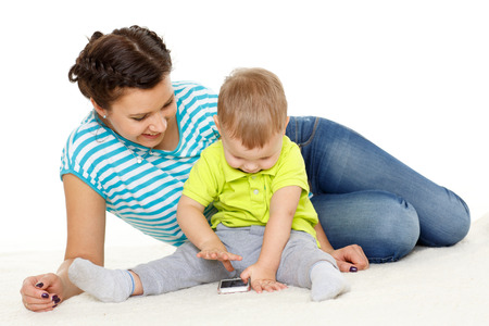Young mother and her little son with mobile phone sit on a white background. Happy family. photo
