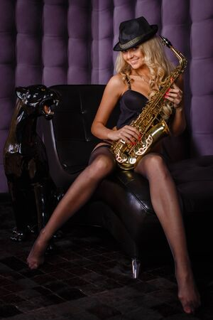 Young beautiful woman with saxophone sits on an armchair in the room. photo