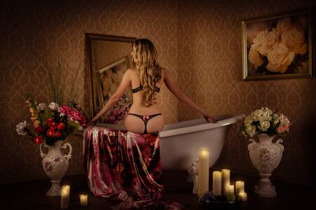 Young beautiful  woman in elegant lingerie sits in a bathroom. Concept body care. photo