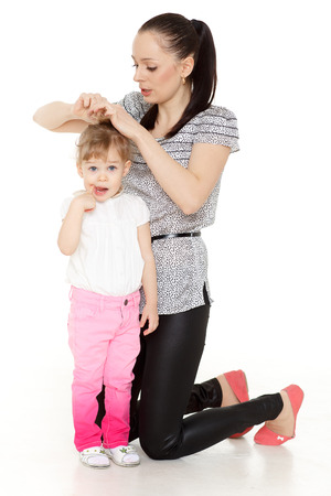 Young mother making hairstyle (ponytail) of the small daughter on a white background. photo