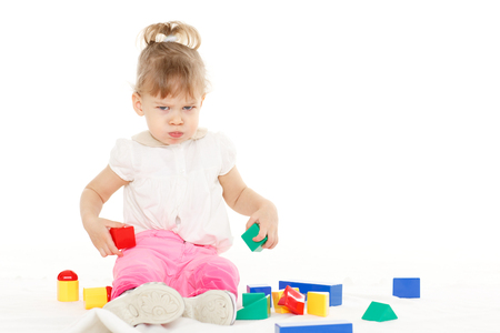 capricious: Little resentful girl plays with children blocks set on a white background. Learning toys and early development. Stock Photo