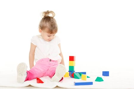 Little pretty girl plays with children blocks set on a white background. Learning toys and early development. photo