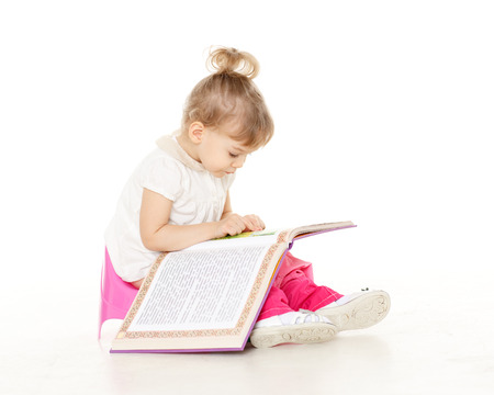 Pretty little girl  with a book sits on a pink baby potty on a white background. Stock Photo