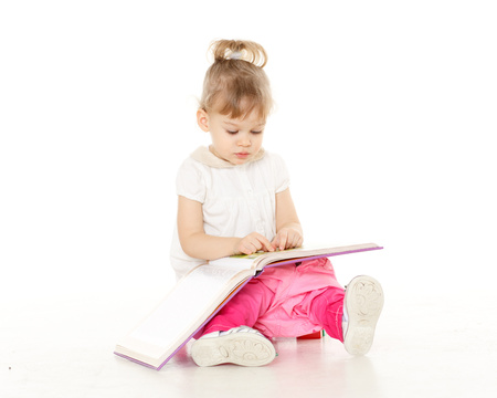 Pretty little girl  with a book sits on a pink baby potty on a white background. photo