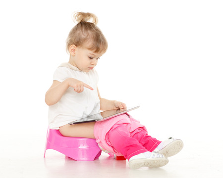potty training: Pretty little girl with computer tablet  sits on a pink baby potty on a white background.