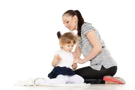 Young mother brushing hair of the small daughter on a white background. photo