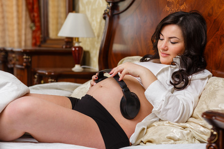 Pregnant woman with headphones lying on the bed and listening to music in the bedroom of the house. photo