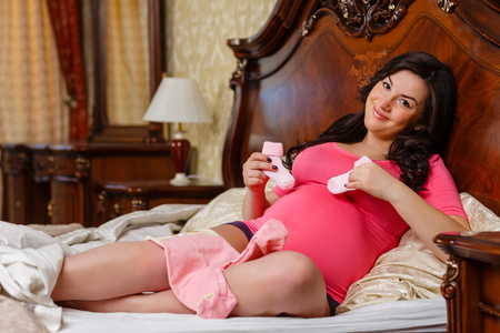 awaiting: Pregnant  woman with childrens clothes sits on the bed in the room.