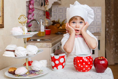 Little girl in apron and cap of the cook with sweet desserts sits at the dining table in the kitchen in the house. Mother's helper. 2 year old. Stock Photo - 27570135