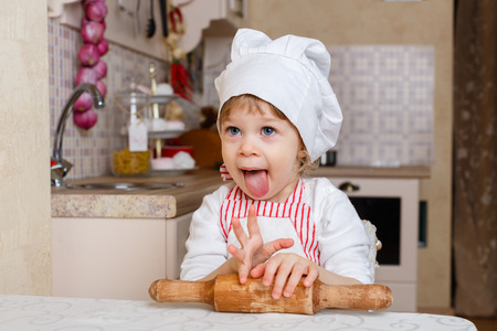Little girl in apron and cap of the cook with rolling pin sits at the dining table in the kitchen in the house. Mother's helper. 2 year old. Stock Photo - 27570134