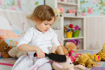 Little girl with hairbrush is playing with toy on the bed in children room. 2 year old. Stock Photo - 27570136