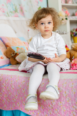 Little girl combing hair sits on the bed in children room. 2 year old. Stock Photo - 27570137
