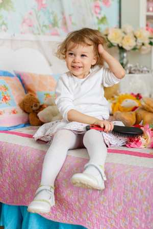 Little girl combing hair sits on the bed in children room. 2 year old. photo