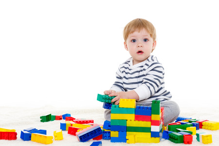 Little sweet boy plays with children blocks set on a white background. Early development and learning toys. photo